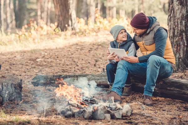 father and son camping using a tablet